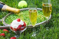 Strawberries with whipped cream, glasses with champagne and tennis equipment on Wimbledon tournament grass. Wimbledon Grand slam celebration concept stock photos