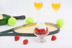 Strawberries with whipped cream, glasses with champagne and  tennis equipment on Wimbledon tournament. Wimbledon Grand slam celebration concept royalty free stock photography