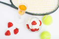 Strawberries with whipped cream, glasses with champagne and  tennis equipment on Wimbledon tournament. Wimbledon Grand slam celebration concept. Top view royalty free stock images