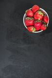 Strawberries in a white bowl on black background Royalty Free Stock Photos