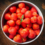 Strawberries in a white bowl. Close-up of red ripe strawberries in a white bowl standing on a wooden table Royalty Free Stock Image