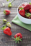 Strawberries in white bowl. Freshly picked strawberries in a white bowl on wooden background Royalty Free Stock Photos