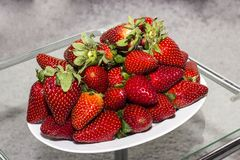 Strawberries. On white bowl and gray background royalty free stock photos