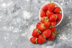 Strawberries in a white bowl on a gray background, top view.  stock images