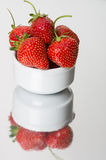 Strawberries in white bowl on metal surface Stock Photos