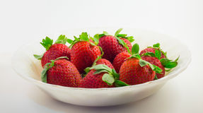Strawberries in the white bowl with white background. Strawberries in a white bowl isolated on the white background Stock Photos