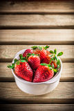 Strawberries in white ceramic bowl on wooden table. Strawberries group in white ceramic bowl on rustic wooden table Stock Photography