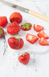 Strawberries on a white chopping board Stock Photo