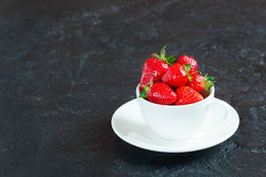 Strawberries in a white cup on a concrete background. Ripe red strawberries in a white cup and saucer on a small concrete background Royalty Free Stock Photography