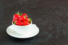 Strawberries in a white cup on a dark background. Ripe red strawberries in a white cup and saucer on a small concrete background Royalty Free Stock Photos