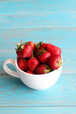 Strawberries in white cup on wooden blue desk. Royalty Free Stock Image