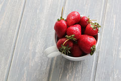 Strawberries in white cup on wooden grey desk. Royalty Free Stock Photography
