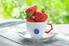 Strawberries in a white decorative Cup on the green blurred background. Royalty Free Stock Image