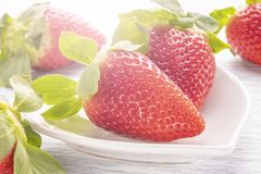 Strawberries on a white dish in the shape of a heart, on a white wooden table royalty free stock photography