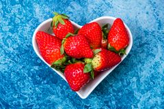 Strawberries in a white heart-shaped dish stock photo
