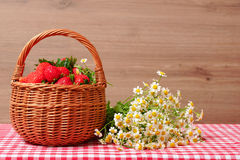 Strawberries in a wicker basket and a bouquet of field chamomiles. Stock Image