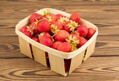 Strawberries in wicker basket. On old rustic wooden planks royalty free stock photos