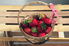 Strawberries in a wicker basket on a striped wooden background Royalty Free Stock Photo