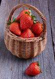 Strawberries in a wicker basket. On the wooden table Stock Photo