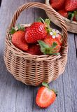 Strawberries in a wicker basket. On the wooden table Royalty Free Stock Image