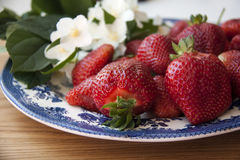 Strawberries on wood. Fresh strawberries on plate, on wood with flowers Royalty Free Stock Photo
