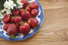 Strawberries on wood. Fresh strawberries on plate, on wood with flowers Royalty Free Stock Images