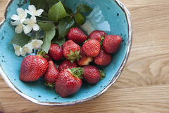 Strawberries on wood. Fresh strawberries on plate, on wood with flowers Royalty Free Stock Photos