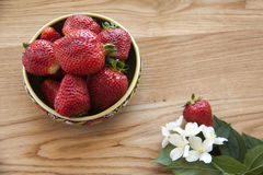 Strawberries on wood. Fresh strawberries on plate, on wood with flowers Royalty Free Stock Image