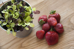 Strawberries on wood. Fresh strawberries on plate, on wood with plant Stock Images