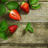 Strawberries on a wooden background. Two and a one half strawberrys on a old wooden background royalty free stock images