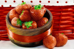 Strawberries In Wooden Bowl. Fresh strawberries in wooden bowl with red basket background stock images