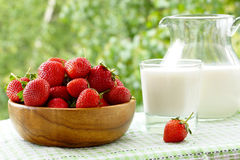 Strawberries in a wooden bowl, a glass and a jug of milk. Strawberries in a wooden bowl, a glass  of milk and a jug of milk. On a table, on background of green Royalty Free Stock Photo