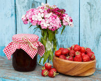Strawberries in wooden bowl and jam. Strawberries in wooden bowl, bunch of garden flowers and jam on wooden plank Royalty Free Stock Image