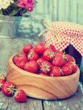 Strawberries in wooden bowl and jam. On wooden plank Stock Image