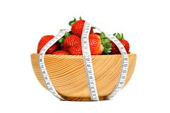 Strawberries in wooden bowl with measuring tape Stock Image