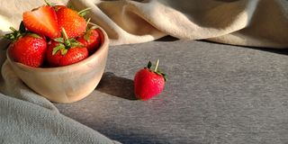 Strawberries on wooden bowl and one on dark background. stock photos