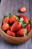 Strawberries in a wooden bowl. Strawberries in a single wooden bowl on wooden table Stock Image