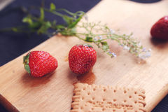 Strawberries on a wooden carving board. Strawberries and cookies on a wooden carving board Stock Photos