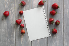 Strawberries on wooden grey desk with white paper sheet. Stock Images