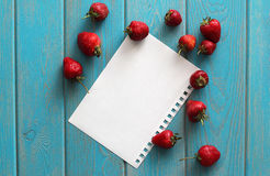 Strawberries on wooden grey desk with white paper sheet. Royalty Free Stock Image