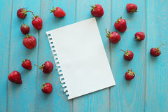 Strawberries on wooden grey desk with white paper sheet. Stock Photo