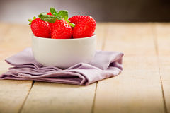 Strawberries on wooden table with violet napkin Royalty Free Stock Image