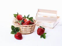 Strawberries in a woven basket over white background Stock Photos