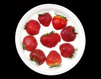 Strawberries and Yogurt. Whole fresh strawberries served in a bowl of yogurt, with one cut and fanned strawberry in the center, isolated on black background stock images