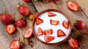 Strawberries yogurt in wood bowl spinning on table stock video