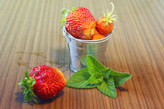 Strawberriesin a small bucket. Tasty strawberry in a small bucket and a mint leaf on a wooden table Stock Photos