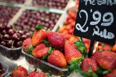 Strawberriews på marknader stannar med pris på en platta Royaltyfri Foto