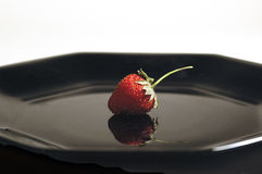 Strawberry. On a black plate stock photos