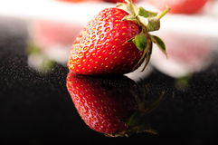 Strawberry. A delicious strawberry on black Royalty Free Stock Images