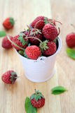 Strawberry. Pink bucket with a strawberry on a wooden board stock photo